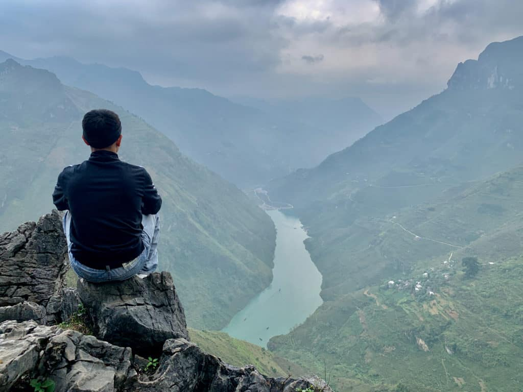 Asian male sitting on rocky peak overlooking Ma Pi Leng Pass in Ha Giang Loop