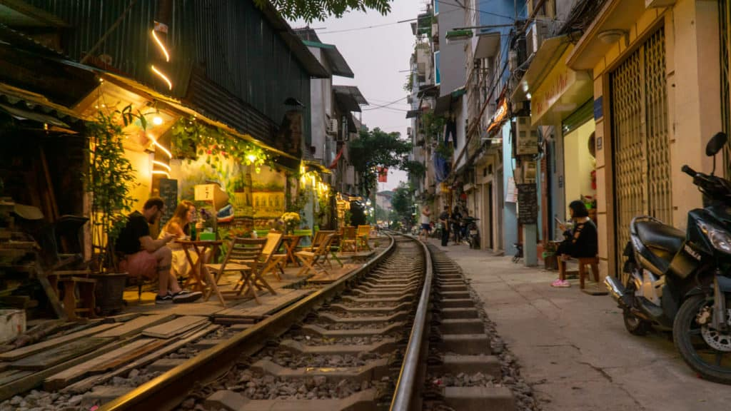 People waiting at cafes on Hanoi Train Street in Vietnam. A popular city attraction is to wait on the train as it comes within inches of the alley walls. One of the best attractions to visit.