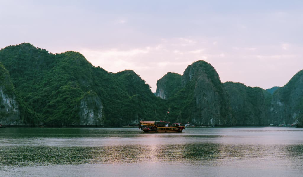 Cat Ba boat tour view of Lan Ha Bay as the sun sets over limestone karst and a tour boat pictured in Vietnam.