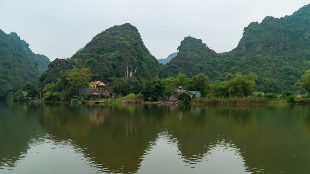 A limestone karst along a river on a foggy day in Trang An City, Vietnam.