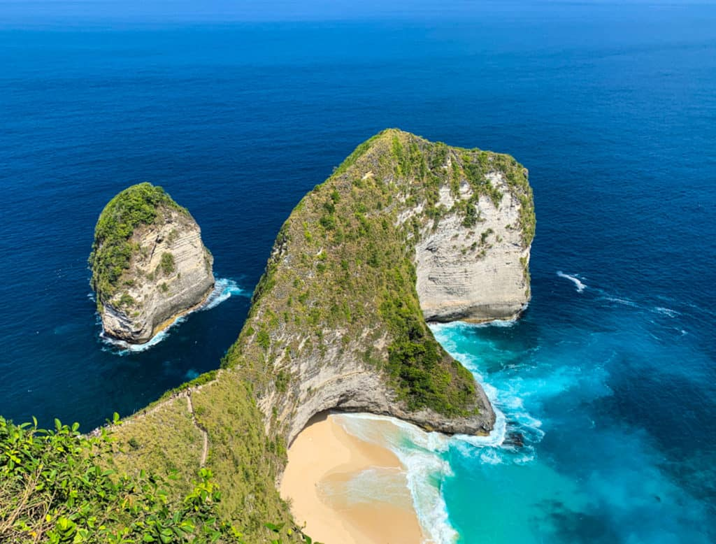 OverlookingKelingking beach from high vantage point. Beautiful blue ocean and rock formation resembling a T-Rex dinosaur in Nusa Penida, Bali, Indonesia.