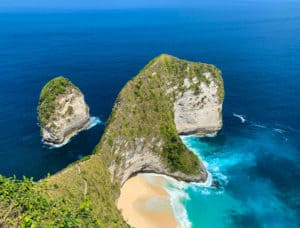 Overlooking Kelingking beach from high vantage point. Beautiful blue ocean and rock formation resembling a T-Rex dinosaur in Nusa Penida, Bali, Indonesia.
