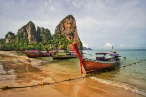 Railay Beach West row of long tail boats in morning